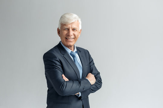 Business Lifestyle. Businessman standing isolated on gray crossed arms smiling confident