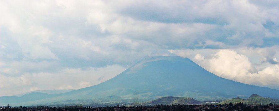 Distant view of Mount Nyiragongo, located in Virunga National Park, in the Democratic Republic of Congo (DRC). It is an active volcano with a lava lake. Mountain peak - landscape with clouds.