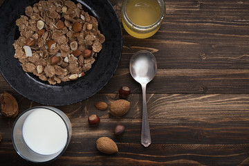 Flat lay of healthy breakfast with nuts and corn flakes on brown rustic background 4