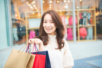Asian Woman Holding Shopping Bags In Shopping Mall