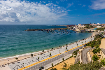 Panorama view over Vasco da Gama beach and town of Sines. Turquoise water. Moody sky, clouds.