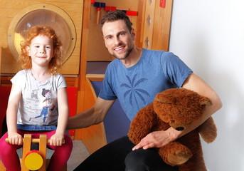 Männlicher Erzieher im Kindergarten mit Kind