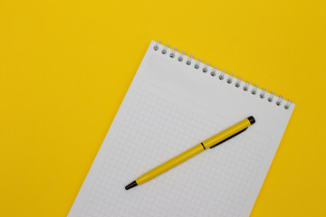 Blank notepad on yellow background with yellow pen.