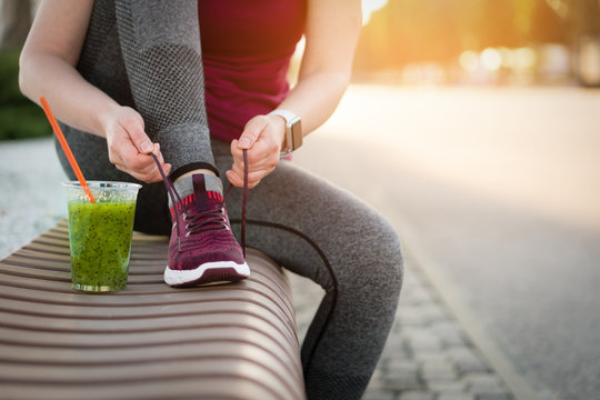 Green detox smoothie cup and woman lacing shoes before workout.