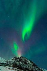 Northern Lights illuminates the sky with mountains of Norway