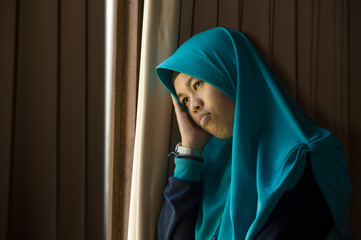 sad and depressed Muslim woman in Islam traditional Hijab head scarf at home window feeling unwell suffering depression crisis and anxiety problem thoughtful and helpless