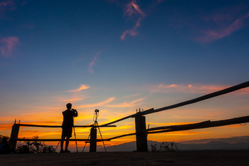 Photographer taking a photo of sunset in silhoustte. Sunset landscape.