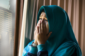 young sad and depressed Muslim woman in Islam traditional Hijab head scarf at home window feeling unwell suffering depression crisis and anxiety problem crying helpless