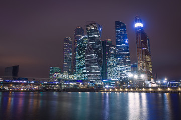 Moscow city night view with skyscrapers and a futuristic bridge over the river