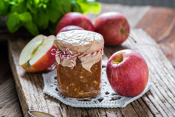 Jar of homemade apple jam, beautifully served on a wooden rustic table