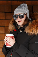 Young hipster woman in a warm knitted hat in sunglasses in a black stylish black jacket with a fur hood and a cup of hot coffee poses near the wooden wall outdoors. Happy girl enjoy the weekend.