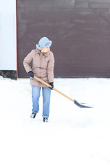 Winter is a lot of snow. A young girl, cleans, proud of doing the big shovel work