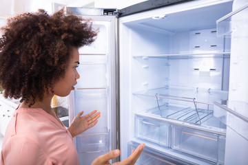 African Woman Looking At Empty Refrigerator