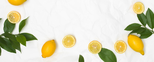 many fresh lemons and green leaves on white crumpled paper background