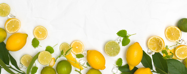 many fresh lemons and limes and green leaves on white crumpled paper background