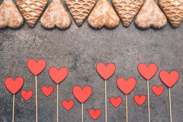 Hearts made of paper placed on sticks and handmade gingerbread. The whole is on an interesting background. The perfect composition for a wedding, Valentine's Day or for lovers.