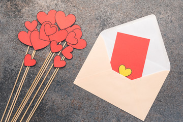 A bouquet made of cut-out red paper hearts. Frame with free, copy space for text or description. Atmospheric, moody background composition with an open envelope.