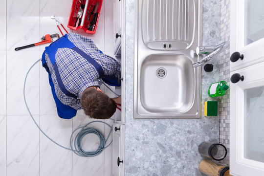 Plumber Cleaning Clogged Sink Pipe