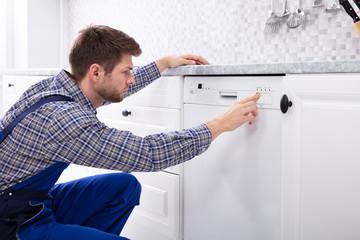Man Pressing Button Of Dishwasher