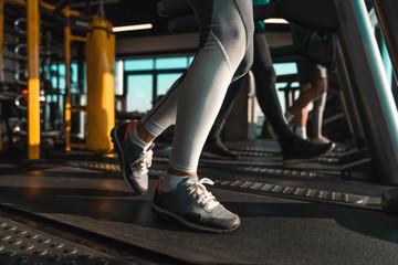Unrecognizable athletes running on treadmills in health club