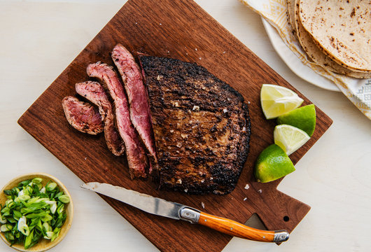 Sliced steak with lime and tortillas