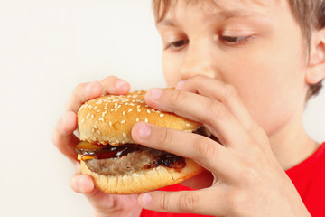 Young cut boy eating a tasty hamburger on a white background close up