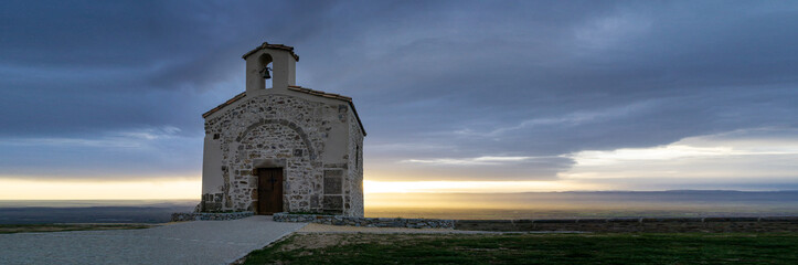 French landscape. Panoramic view over the Rhone valley to the Vercors and the Alps in the background at sunrise and small chapel in the foreground.