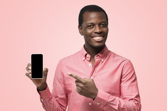 Handsome african man in pink shirt presenting smart phone and pointing with finger at blank black screen with copyspace for your app
