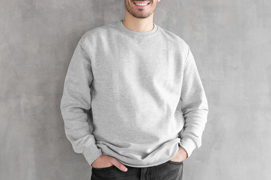 Mock up shot of young man body in empty sweatshirt isolated on textured gray wall background. No face photo