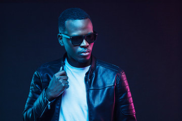 Neon studio portrait of african american man wearing trendy sunglasses and leather jacket Wall mural
