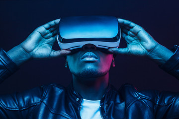 Portrait of African guy isolated on black background wearing headset of virtual reality
