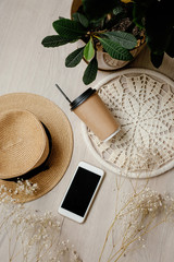 Flat Lay photo with smartphone, paper coffee cup, straw hat, plant and fllowers