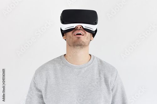 049f332e419 Studio portrait of astonished young man in virtual reality glasses. VR  concept