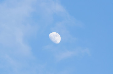 Half bright moon on blue sky background with clouds on day time