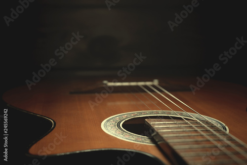 Part Of An Old Brown Guitar With Strings On A Dark Wooden Background