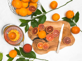 beautiful still life with blood oranges on white paper background and wooden board and knife