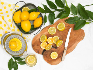 beautiful still life with lemons on white paper background and wooden board and knife