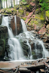 beautiful two cascaded waterfall among the forest. wonderful nature scenery in spring or summer. fallen foliage on the ground. huge boulders. refreshing stream