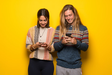 Hippie couple over yellow background sending a message with the mobile