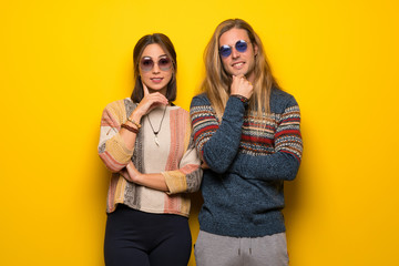 Hippie couple over yellow background with glasses and smiling