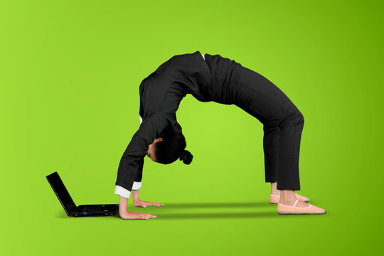 Businesswoman uses a laptop with back bend pose