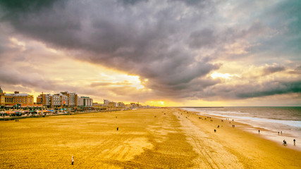 Beautiful seaside landscape - view of the beach near the embankment of The Hague with people making promenade, the Netherlands