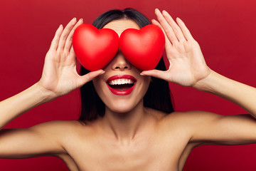 Cheerful exited brunette woman holding hearts. Valentine's Day portrait of attractive smiling woman isolated on red studio shot with hearts