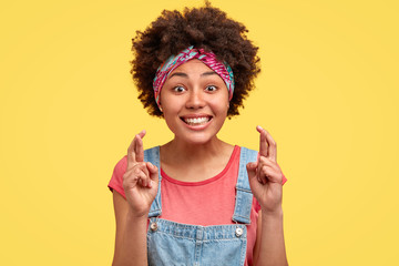 Inspired woman makes wish with crossed fingers, has hopeful look, smiles broadly, gestures with both hands, wears denim overalls, isolated over yellow background, believes in good luck and fortune