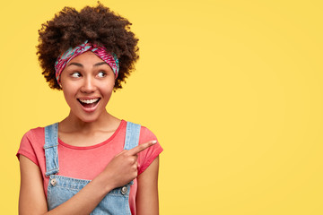 Satisfied curly female seller being in good mood, wears headband, dungarees, shows direction with index finger, models against yellow wall with blank space for your advertising content or promotion