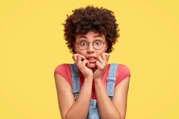 Headshot of frustrated mixed race young woman has crisp hair, bites finger nails with nervous expression, stares with eyes full of fear, wears casual clothes, stands against yellow studio wall