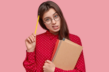Daily schedule and checklists of tasks. Puzzled young woman scratches head with pencil, thinks what is done, writes notes in notepad, has thoughtful expression, isolated over pink background