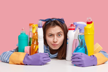 Horizontal shot of indignant young woman does housework, raises eyebrows and looks surprisingly at camera, wears rubber protective gloves and headand, looks through bottles of cleaning agents