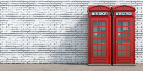 Red phone booth on brick wall background. London, british and english symbol.
