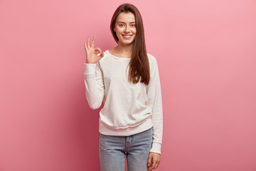 Indoor shot of good looking brunette woman customer shows great sign, satisfied with good quality of product, dressed in casual clothes, models against pink background. Girl demonstrates zero sign Wall mural